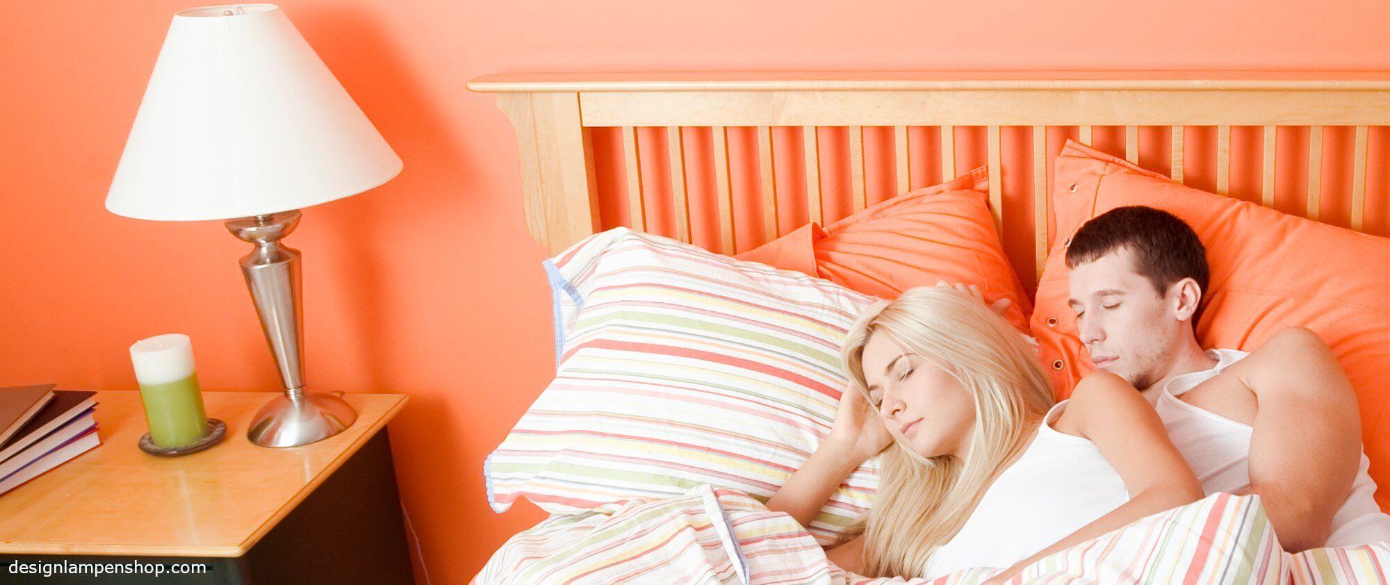 Junges Paar im Schlafzimmer mit Nachttischlampe